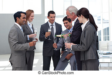 Senior businessman serving Champagne to his successful team...