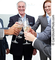 Cheerful business team celebrating a success with Champagne