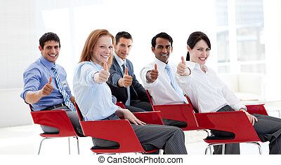 Business people with thumbs up at a conference. Business...