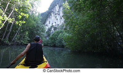 old man paddles on kayak to cliff among jungle