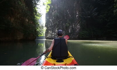 old man paddles on kayak out to light among cliffs - old man...
