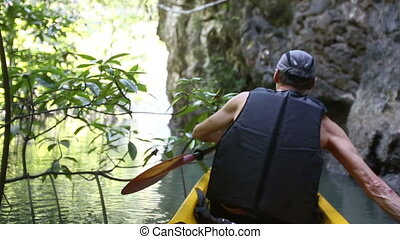 man backside view rows on kayak in canyon - european man...