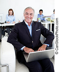 Smiling businessman using a laptop with his team in the...