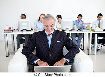 Senior businessman using a laptop with his team in the...