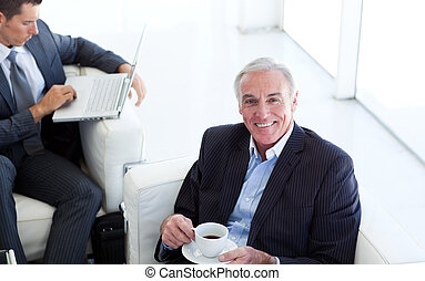 Senior businessman drinking coffee and waiting for a job interview in an office