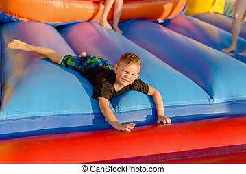 Small blonde boy lying on bouncy castle