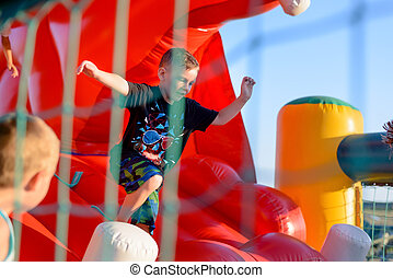 Small boy playing on bouncy castle - Small blonde boy (6-8...