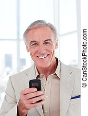 Senior businessman using a mobile phone and smiling at the...