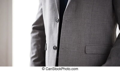 close up of man in suit fastening button on jacket - people,...