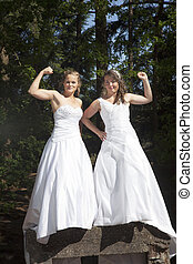 picture of two brides standing on concrete object in nature surroundings
