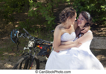 two brides on bench in forest with mountain bikes - two...