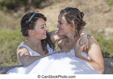 two brides smile and embrace in nature surroundings on sunny...