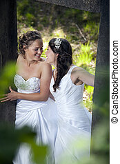 romantic picture of two brides in nature surroundings -...