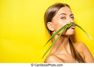 green onion - Joyful young woman with green onion over...