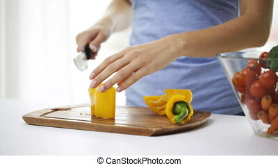 close up of young woman chopping pepper at home - healthy...