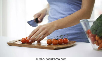 close up of young woman chopping tomatoes at home - healthy...