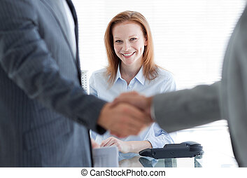 Businesswoman smiling with businessmen greeting each other...