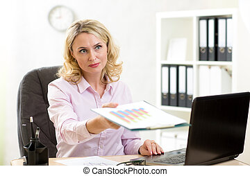 Smiling mature business lady giving paper to colleague