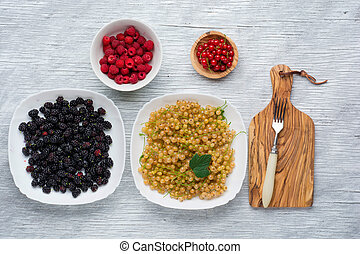 tasty summer fruits on a wooden table. raspberries, Blackberries, mulberry, currant, red and yellow currant,