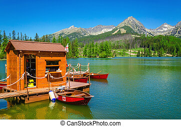 Wooden hut and red boats on mountain lake - Wooden hut and...