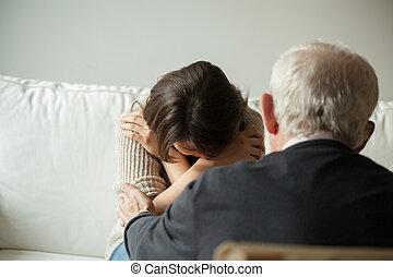Grandpa comforting his crying granddaughter - Horizontal...