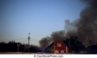 Fire burning and black smoke over the house.