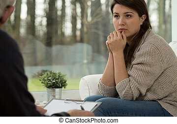 Young woman on psychotherapy session - Young sad woman being...