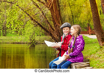 Smiling girl and boy sit near nice pond playing - Smiling...