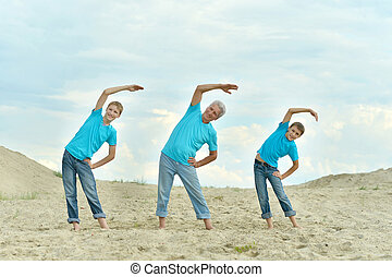 elderly man with grandson charge on the beach