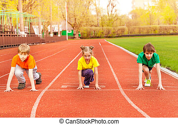 Three kids stand with bended knee ready to run - Three kids...