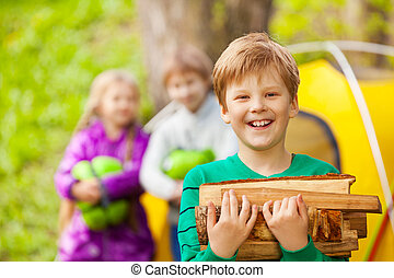 Portrait of happy boy holding the wood for bonfire
