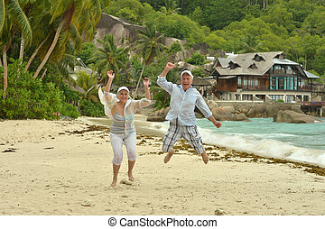 elderly couple jumping on the beach