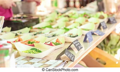 Raw food festival - A person taking business card from the...