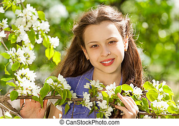 Attractive teenager girl with white pear flowers -...