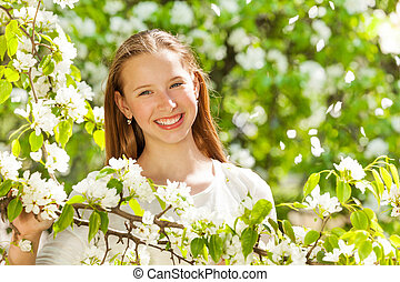 Happy teenager girl with white flowers on tree - Happy...