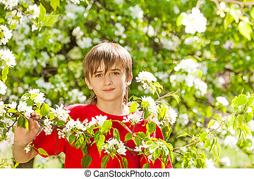 Teenager boy holds branch with white flowers on pear tree...