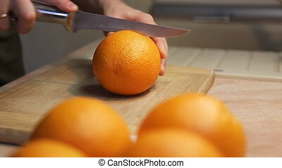 Mans hands cutting fresh orange on - Hands cutting fresh...