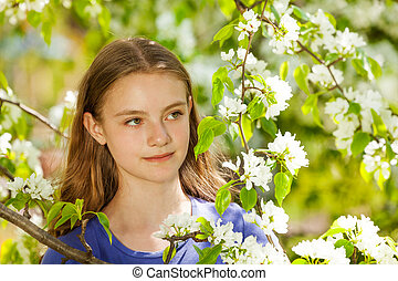 Pretty teenager girl with white pear flowers - Looking...