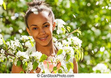 African teenager girl with flowers on pear tree - African...