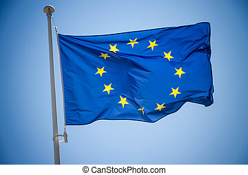 European Union flag on blue sky background, close up