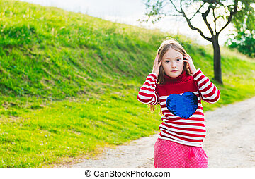 Outdoor portrait of a cute little girl of 7 years old at sunset, wearing red pullover,