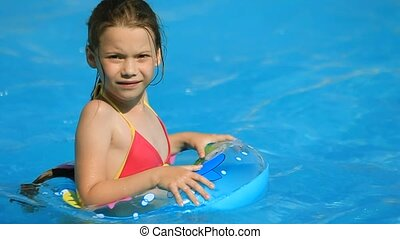 Pool Games - Girl in aqua Park looks. Child swims with her...