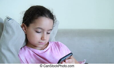 Girl on a couch using mobile phone - Cute girl with her...