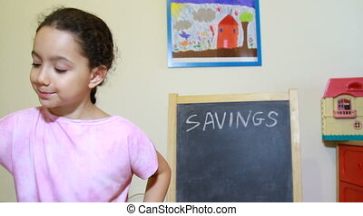 Saving education concept - Girl putting money into savings...