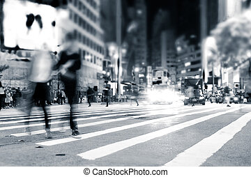 People moving in crowded night city street. Hong Kong -...