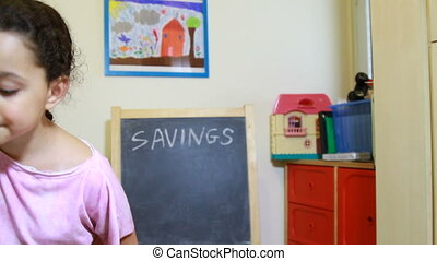 ids saving money concept - Girl save by putting money in...