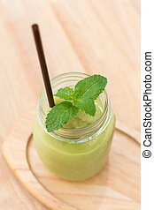 fruit and vegetable green smoothie on a wooden table, close-up