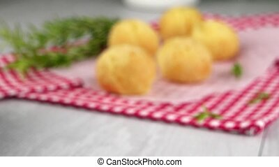 Brazilian cheese buns over red towel on wooden table.