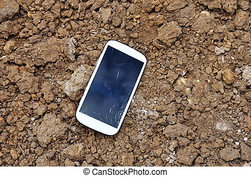 Cell phone On Soil Surface. - White Cell phone On Soil...