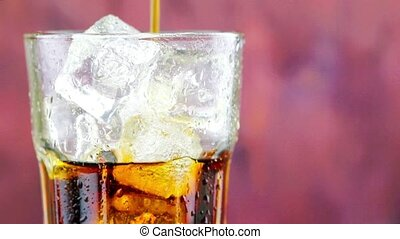 pouring fresh coke with ice cubes into glass with drops on...